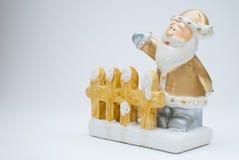 Figurina all'antica dorata di Santa Claus che sta dietro il recinto del giardino e che ondeggia con una mano, colpo in studio fotografie stock libere da diritti
