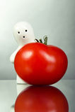 Figurina bianca del ricordo con il pomodoro rosso Fotografia Stock