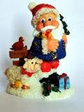 Figurina ceramica miniatura di Santa Claus allegra isolata su fondo bianco che porta i regali e desidera tutto il Buon Natale! immagini stock libere da diritti