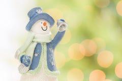 Figurina del pupazzo di neve su neve sopra un fondo astratto confuso Fotografia Stock Libera da Diritti
