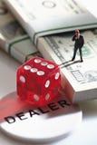 Figurina del responsabile che sta su un pacco di 100 note del dollaro americano con i dadi Fotografia Stock Libera da Diritti