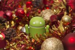 Figurina di Android con la ghirlanda di natale Fotografia Stock