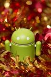 Figurina di Android con la ghirlanda di natale Fotografie Stock Libere da Diritti