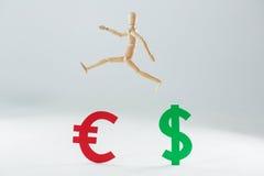Figurina di legno che salta sopra il simbolo dell'euro e del dollaro Immagine Stock