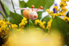 Figurina di legno delle api nei fiori Fotografie Stock Libere da Diritti