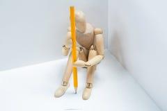 Figurina di legno tesa con una seduta della matita Immagine Stock Libera da Diritti