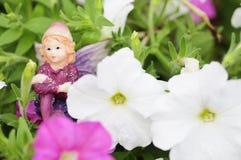 Figurina di un fatato visualizzato fra le petunie bianche e rosa Immagini Stock