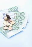 Figurina maschio che si siede sulla pila di euro monete e note Immagine Stock