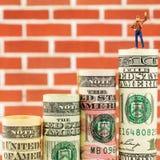 Figurina miniatura con il gesto di vittoria sulla maggior parte della banconota americana stimata del dollaro Immagini Stock