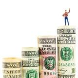 Figurina miniatura con il gesto di vittoria sulla maggior parte della banconota americana stimata del dollaro Fotografia Stock Libera da Diritti