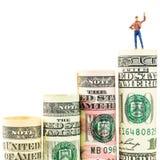 Figurina miniatura con il gesto di vittoria sulla maggior parte della banconota americana stimata del dollaro Immagine Stock