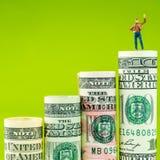 Figurina miniatura con il gesto di vittoria sulla maggior parte della banconota americana stimata del dollaro Fotografia Stock