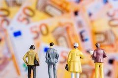 Figurina miniatura con protagonista al grande nuovo banknot defocused dell'euro 50 Fotografie Stock Libere da Diritti
