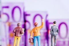 Figurina miniatura con protagonista alle grandi euro banconote defocused Immagine Stock Libera da Diritti