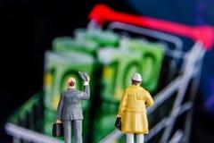 Figurina miniatura con protagonista alle grandi euro banconote defocused Fotografia Stock Libera da Diritti
