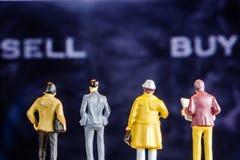 Figurina miniatura con protagonista alle grandi parole defocused dell'affare e di vendita Fotografie Stock