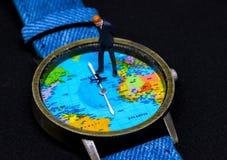 Figurine бизнесмена на вахте Часы карты мира принципиальная схема дела всемирная Стоковая Фотография