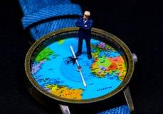 Figurine бизнесмена на глобальном вахте карты принципиальная схема дела всемирная Стоковые Фотографии RF