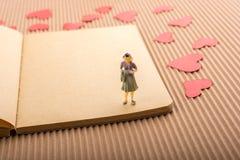 Figurine женщины и концепция влюбленности с бумажными сердцами стоковая фотография
