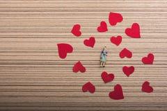 Figurine женщины и концепция влюбленности с бумажными сердцами стоковые изображения