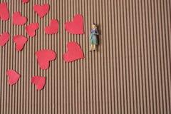 Figurine женщины и концепция влюбленности с бумажными сердцами стоковая фотография rf