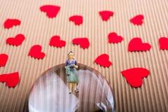 Figurine женщины на половине глобуса с бумажными сердцами стоковое изображение rf