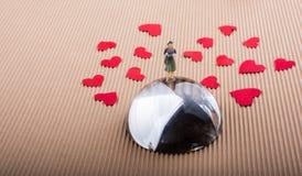 Figurine женщины на половине глобуса с бумажными сердцами стоковые изображения