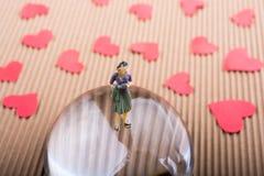 Figurine женщины на половине глобуса с бумажными сердцами стоковые фото