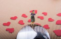 Figurine женщины на половине глобуса с бумажными сердцами стоковое изображение
