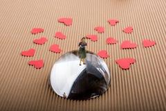 Figurine женщины на половине глобуса с бумажными сердцами стоковые изображения rf