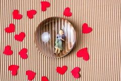 Figurine женщины под половиной глобуса с бумажными сердцами стоковые изображения rf