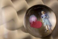 Figurine женщины под половиной глобуса с бумажными сердцами стоковое фото