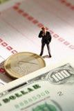 Figurine менеджера стоя на держа пари выскальзывании с монеткой евро и примечанием 100 долларов США Стоковые Изображения