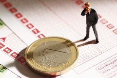 Figurine менеджера стоя на держа пари выскальзывании с монеткой евро, конце вверх Стоковое Изображение RF