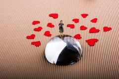 Figurine женщины на половине глобуса с бумажными сердцами стоковое фото rf