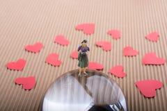 Figurine женщины на половине глобуса с бумажными сердцами стоковые фотографии rf