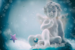 Figurine of an angel in blurred background Stock Photos
