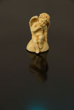 A figurine of an angel of a child with wings of yellow clay on a Royalty Free Stock Images