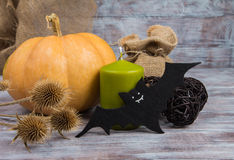 Figurine bat, pumpkin and green candle on autumn background. Halloween decorations Stock Images