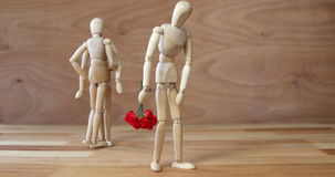 Figurine with bunch of roses jealous with other couple. On wooden background stock video