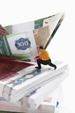 Figurine on bundles of euro notes with paper boat Royalty Free Stock Images