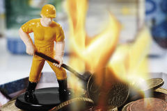 Figurine burning money, close up Royalty Free Stock Image