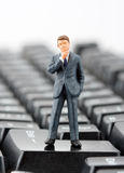 Figurine of businessman on keyboard Royalty Free Stock Images