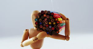 Figurine carrying bunch of colored pencil. Conceptual image of figurine carrying bunch of colored pencil stock video footage