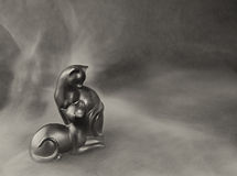Figurine cats in a fog on a dark background. Royalty Free Stock Photo