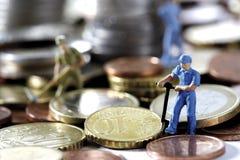 Figurine che scavano soldi, primo piano Fotografie Stock