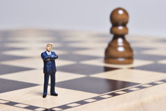 Figurine and chess. Business figurine placed on chessboard with chess pieces royalty free stock photos