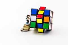 Figurine on coins climbing on rubik cube Royalty Free Stock Photo