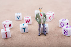 Figurine and the colorful alphabet letter cubes Royalty Free Stock Photo
