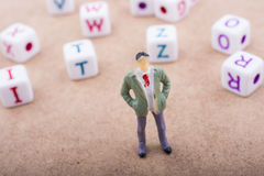 Figurine and the colorful alphabet letter cubes Royalty Free Stock Photography